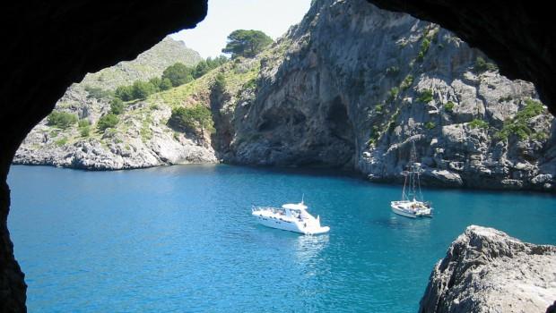 Mer et voiliers vu depuis une grotte dans la falaise